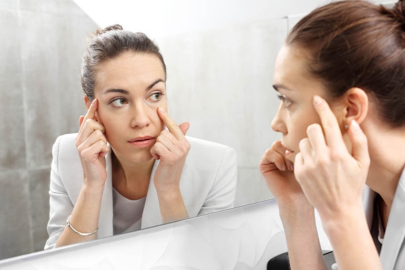 Woman examining her face in the mirror, in need of a good skin care routine