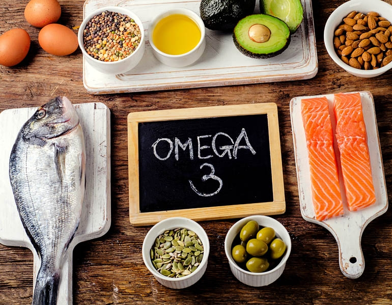 A table full of Omega 3 EPA rich foods including raw fish, olives, avocado, almonds, eggs and more