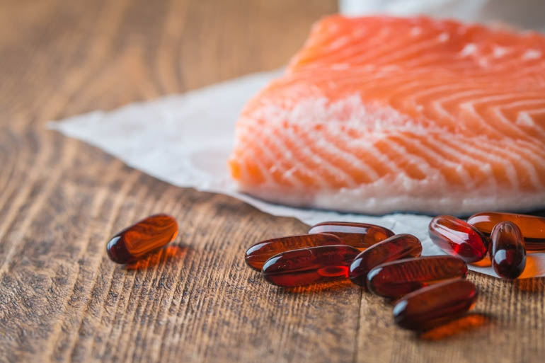 Fish Oil pills next to a piece of fresh salmon