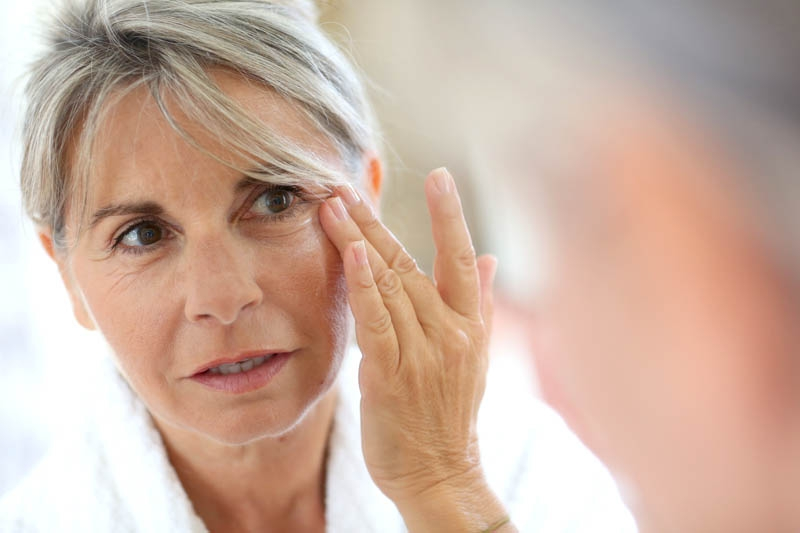 An older woman pulling at her wrinkles in the mirror. Dorinda James makes facial products to help stop the effects of aging.