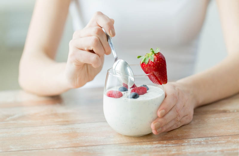 woman eating a cup of yogurt, a source of probiotics