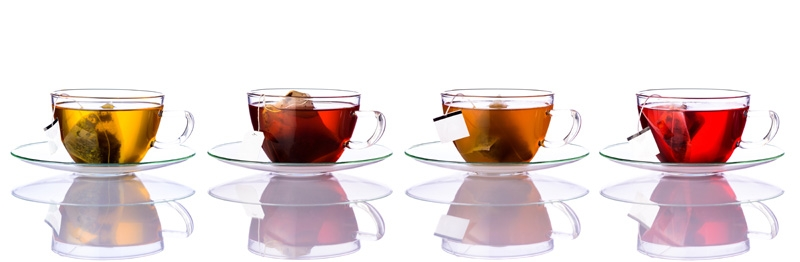 Four glasses of tea in a row, each with their own tea bag and unique coloring