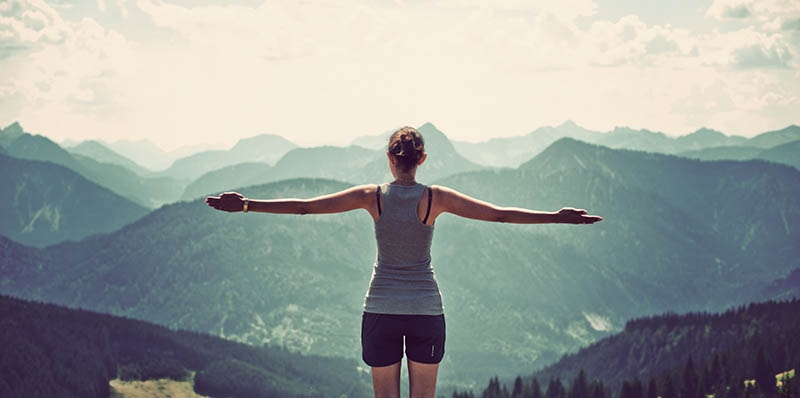 Healthy woman on a mountaintop with arms outstretched- healthy living at it's peak with Glutathione