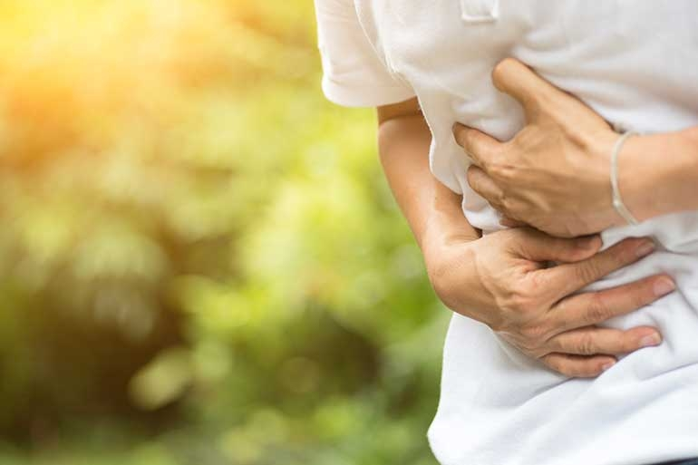 Man grasping gut with chronic inflammation of the intestinal tract