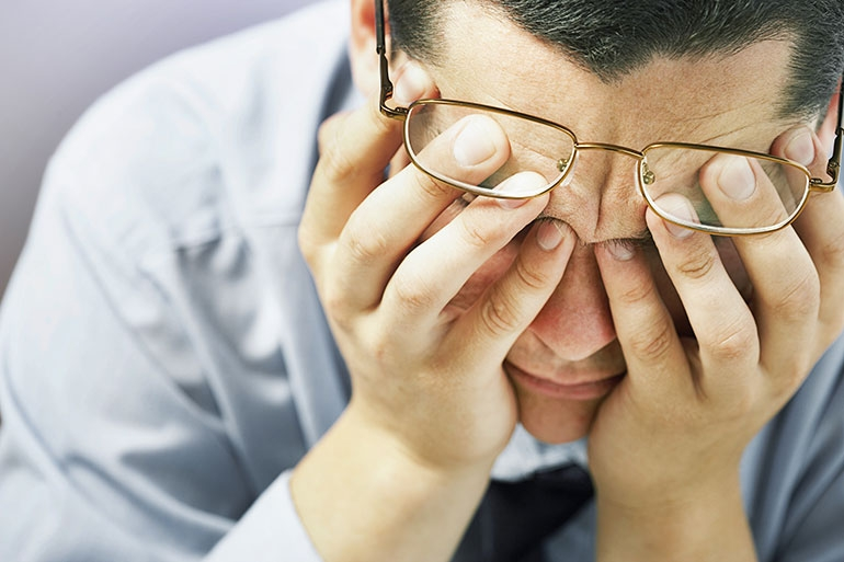 Man with head in hands feeling stressed