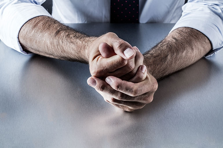 A man clutching hands together in stress