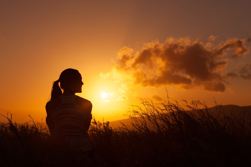 A woman sitting watching a sunset- having a brighter view on estrogen and hormone balance