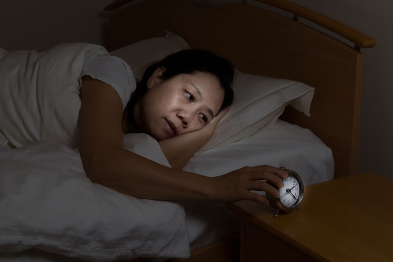 Woman lying in bed awake at night grasping for the alarm clock- apparently having trouble sleeping