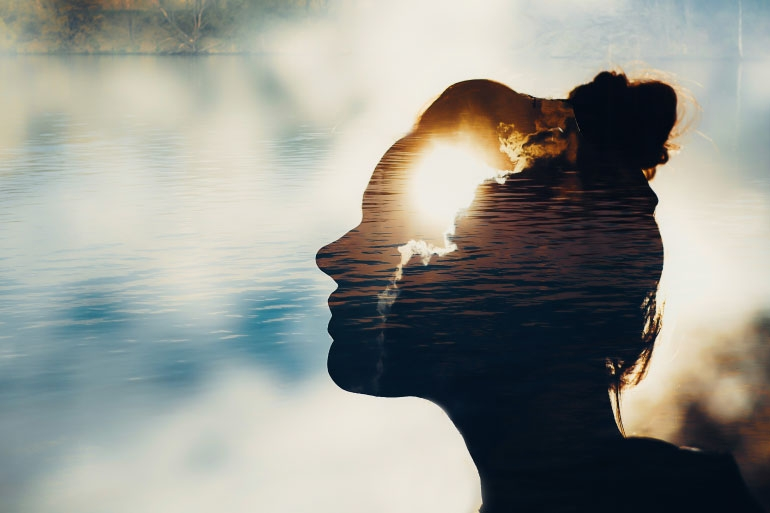 Silhouette of a woman with water, clouds and sun shine representing neurotransmitters in the brain