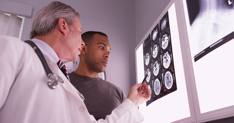 A doctor and TBI patient looking over brain x rays. Discuss a nutritional treatment plan with your doctor or wellness expert today.